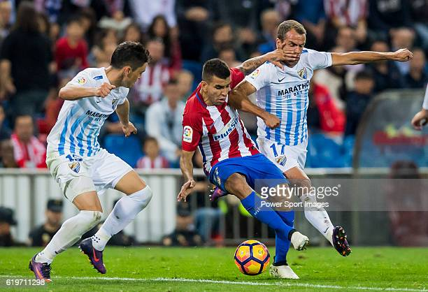 Angel Correa of Club Atletico de Madrid fights for the ball with Federico Ricca Rostagnol and Duda of Malaga CF during their La Liga match between...