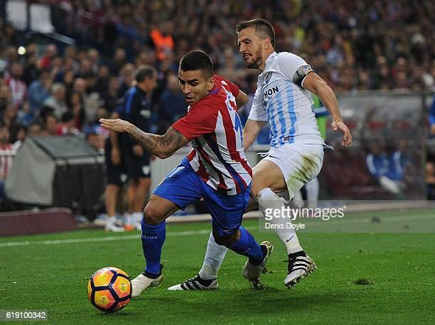 Angel Correa of Club Atletico de Madrid gets past Ignacio Camacho of Malaga CF during the La Liga match between Club Atletico de Madrid and Malaga CF...