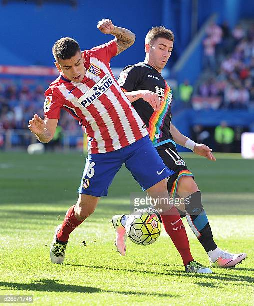 Angel Correa of Club Atletico de Madrid is tackled by Adrian Embarba of Rayo Vallecano during the La Liga match between Club Atletico de Madrid and...