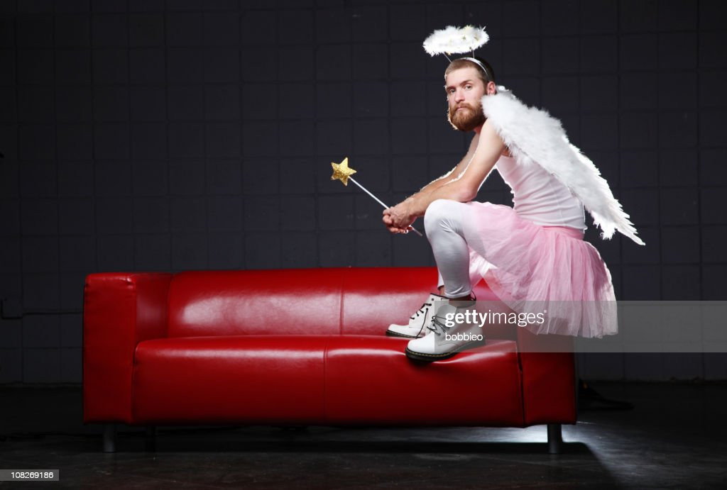 angel costume man sitting on couch stock photo getty images. Black Bedroom Furniture Sets. Home Design Ideas