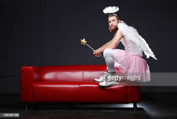 angel: costume man sitting on couch - fairy stock photos and pictures