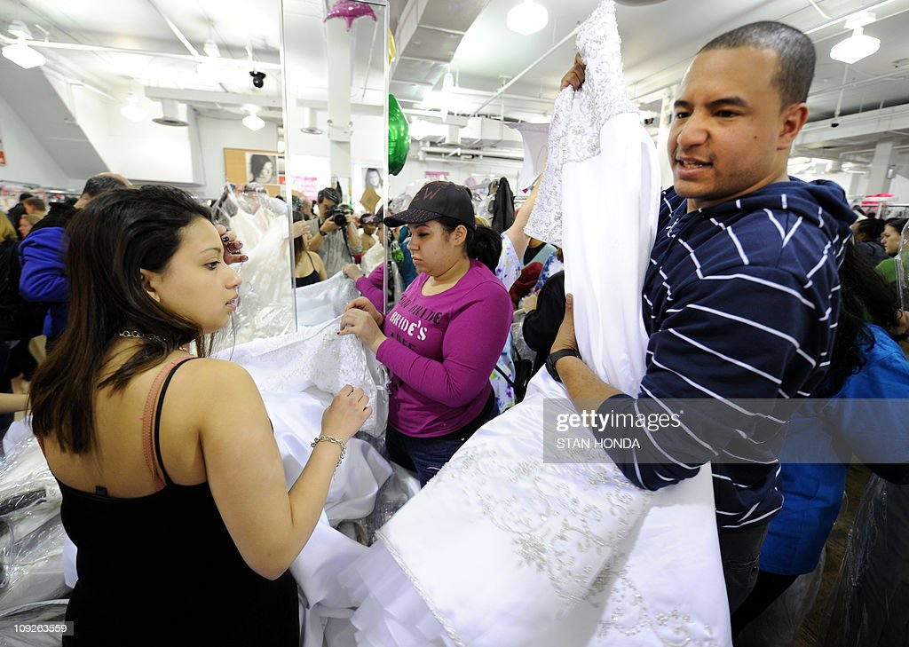 Angel Crespo (R) brings a wedding gown t Pictures   Getty Images