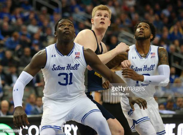 Angel Delgado and Myles Powell of the Seton Hall Pirates hold back Harry Froling of the Marquette Golden Eagles during a game at Prudential Center on...