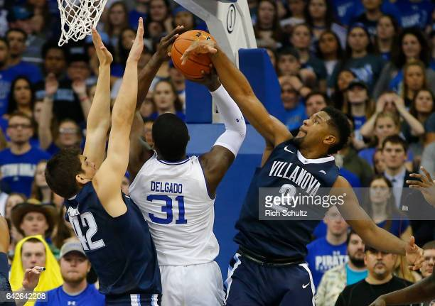 Angel Delgado of the Seton Hall Pirates attempts a shot between Dylan Painter and Kris Jenkins of the Villanova Wildcats during the first half of an...