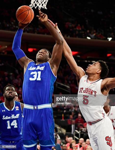 Angel Delgado of the Seton Hall Pirates attempts a shot defended by Justin Simon of the St John's Red Storm during the first half of an NCAA...