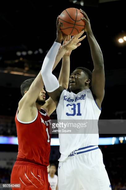 Angel Delgado of the Seton Hall Pirates attempts a shot while being guarded by Omer Yurtseven of the North Carolina State Wolfpack in the second half...