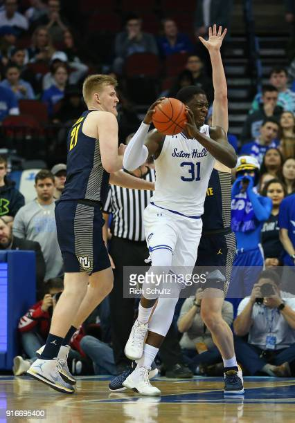 Angel Delgado of the Seton Hall Pirates is defended by Harry Froling and Sam Hauser during a game at Prudential Center on February 7 2018 in Newark...