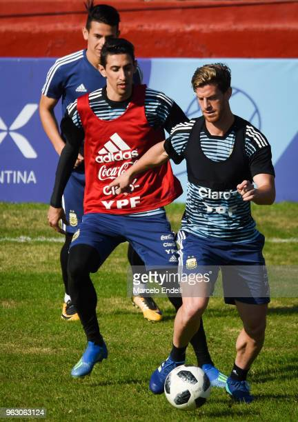 Angel Di Maria and Cristian Ansaldi compete for the ball during a training session open to the public as part of the team preparation for FIFA World...