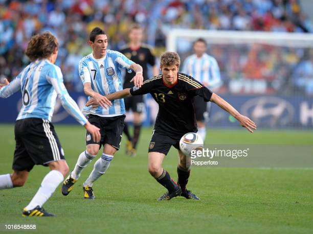 Angel Di Maria of Argentina and Thomas Mueller of Germany in action during the 2010 FIFA World Cup Quarter Final match between Argentina and Germany...