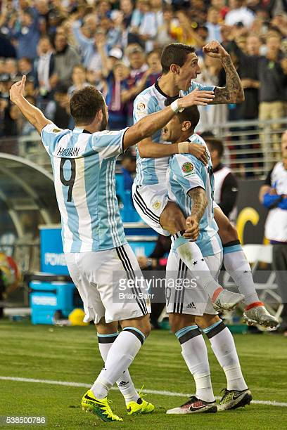 Angel Di Maria of Argentina celebrates with Ever Banega and Gonzalo Higuain after scoring the first goal against Chile in the second half during a...