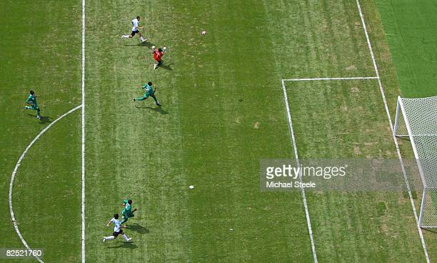 Angel Di Maria of Argentina chips in the opening goal past goalkeeper Ambrose Vanzekin of Nigeria in the Men's Gold Medal football match between...