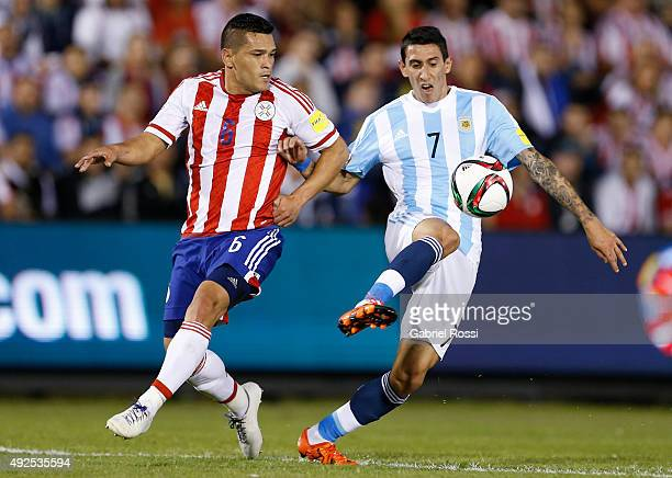 Angel Di Mar'ia of Argentina fights for the ball with Miguel Samudio of Paraguay during a match between Paraguay and Argentina as part of FIFA 2018...