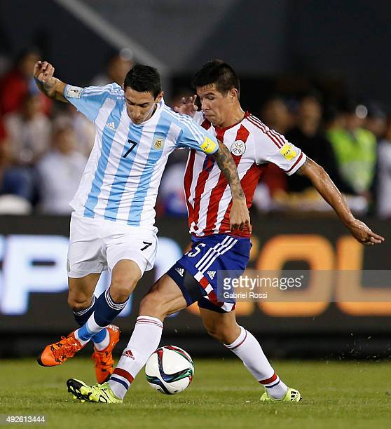 Angel Di Mar'ia of Argentina fights for the ball with Victor Caceres of Paraguay during a match between Paraguay and Argentina as part of FIFA 2018...