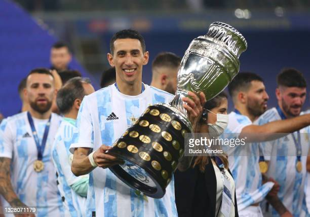 Angel Di Maria of Argentina poses with the trophy after winning the final of Copa America Brazil 2021 between Brazil and Argentina at Maracana...
