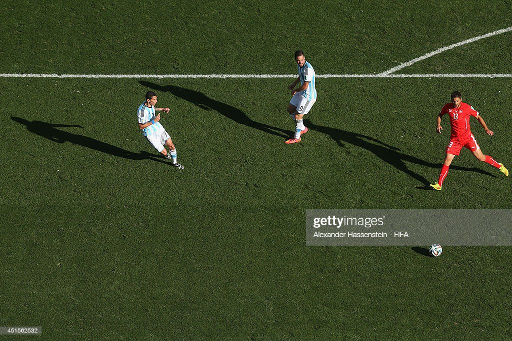 Angel di Maria (L) of Argentina scores his team's first goal in extra time against Ricardo Rodriguez (R) of Switzerland during the 2014 FIFA World Cup Brazil Round of 16 match between Argentina and Switzerland at Arena de Sao Paulo on July 1, 2014 in Sao Paulo, Brazil.