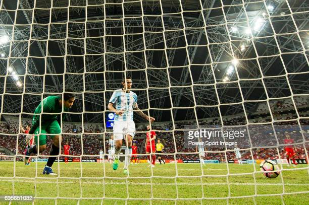Angel Di Maria of Argentina scoring his goal while being observed by Izwan Mahbud of Singapore during the International Test match between Argentina...