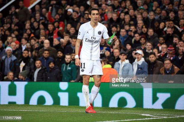 Angel Di Maria of Paris SaintGermain holds a bottle of beer thrown by the fans during the UEFA Champions League Round of 16 First Leg match between...