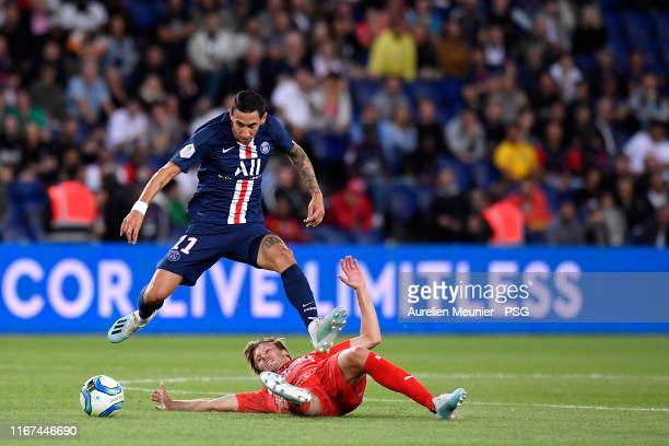 Angel Di Maria of Paris Saint-Germain is tackled during the Ligue 1 match between Paris Saint-Germain and Nimes Olympique at Parc des Princes on...
