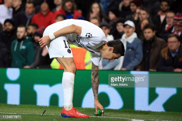 Angel Di Maria of Paris SaintGermain stoops to pick up a bottle of beer thrown by the fans as a lighter lands behind him during the UEFA Champions...