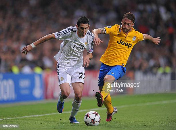 Angel Di Maria of Real Madrid CF is challenged by Claudio Marchisio of Juventus during the UEFA Champions League Group B match between Real Madrid CF...