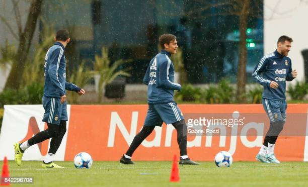Angel Di Maria Paulo Dybala and Lionel Messi of Argentina warm up during a training session at 'Julio Humberto Grondona' training camp on September...
