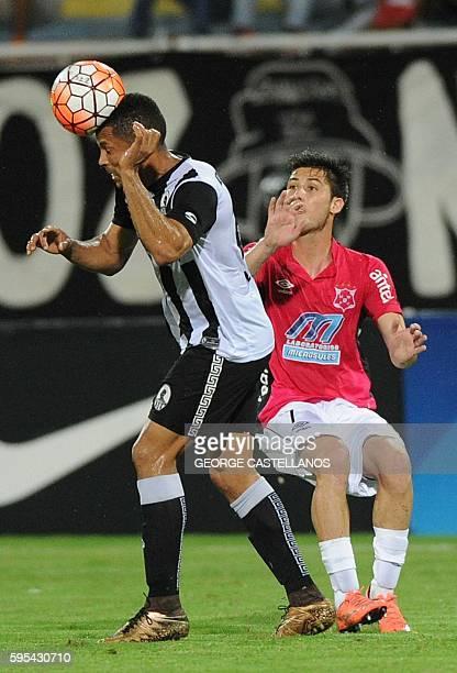 Angel Faria of Venezuela's team Zamora heads the ball as Rodrigo Rivero of Uruguay's Wanderers looks on during their Sudamericana Cup football match...
