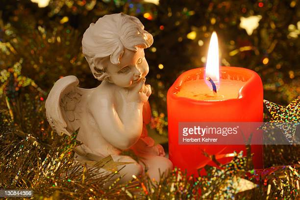 Angel figurine beside a burning candle, Christmas decoration