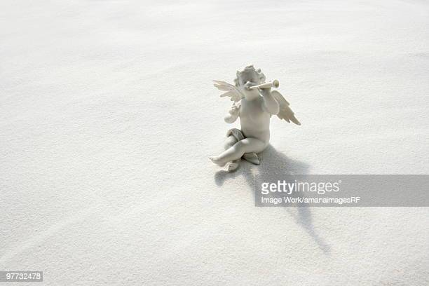 Angel figurine with musical instruments on white sand