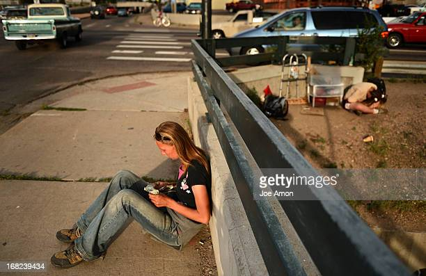 Angel Gamboeck counts the money she has made from panhandling hoping she made enough to call her dealer while Amanda Rose Landry hunches over from...