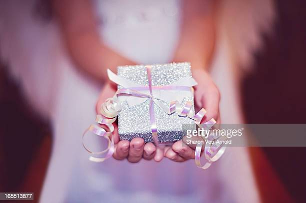 Angel girl holding a beautifully wrapped gift