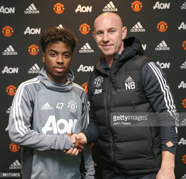 Angel Gomes of Manchester United poses with Nicky Butt after signing his first professional contract with the club at Aon Training Complex on...
