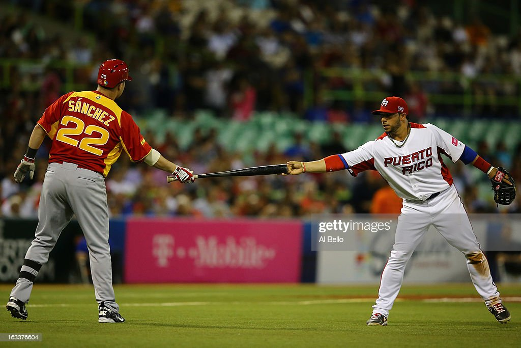 Angel Gonzalez #26 of Puerto Rico hands the bat back to Yunesky Sanchez #22 of Spain after it slipped out of his hand during the first round of the World Baseball Classic at Hiram Bithorn Stadium on March 8, 2013 in San Juan, Puerto Rico.