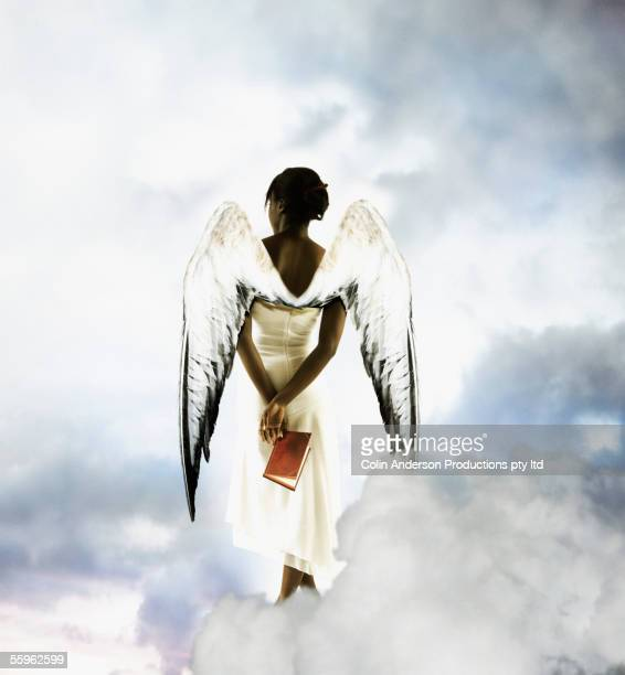 Angel in clouds holding book