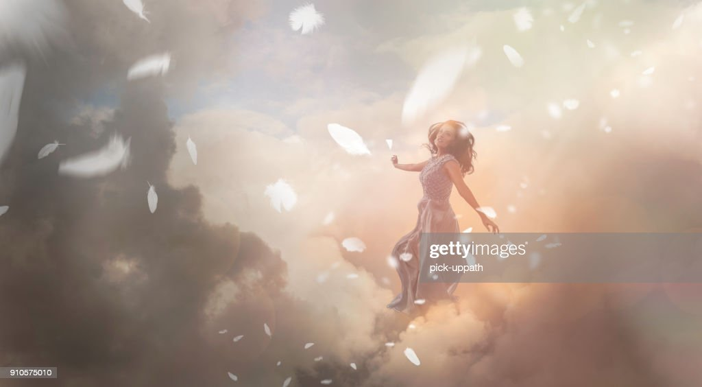 Angel in sky with falling feathers : Stock Photo