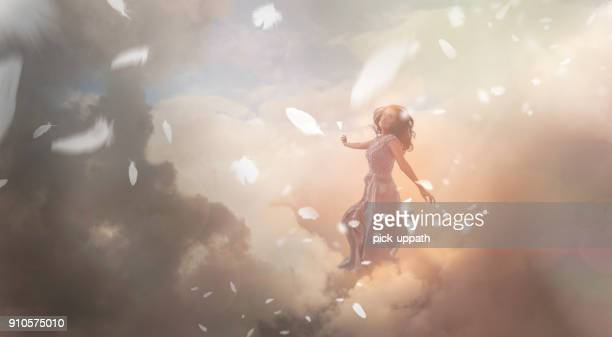angel in sky with falling feathers - elysium stock photos and pictures