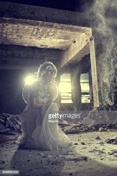 Angel in white dress posing in a ruin.