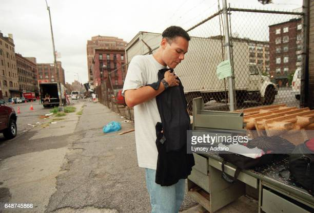 Angel inspects women's clothing on the streets of New York City in 1999