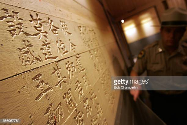 Angel Island park superintendent Dave Matthews holding protective plastic covering passes Poem 69 carved into the wall where detainees recorded their...
