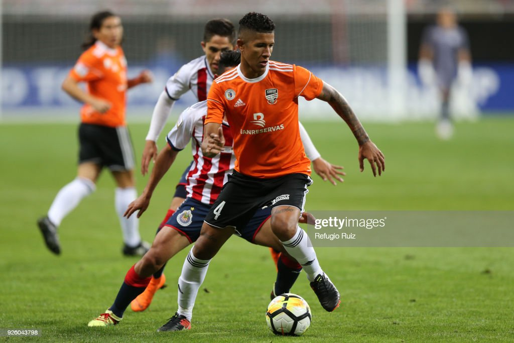 Angel Lopez of Chivas fights for the ball with Richard Dabas of Cibao during the match between Chivas and Cibao as part of the round of 16th of the CONCACAF Champions League at Akron Stadium on February 28, 2018 in Zapopan, Mexico.