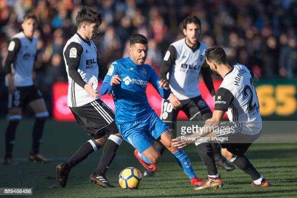 Angel Luis Rodriguez Diaz of Getafe CF fights for the ball against Carlos Soler Barragan of Valencia CF Daniel Parejo Munoz of Valencia CF and Martin...