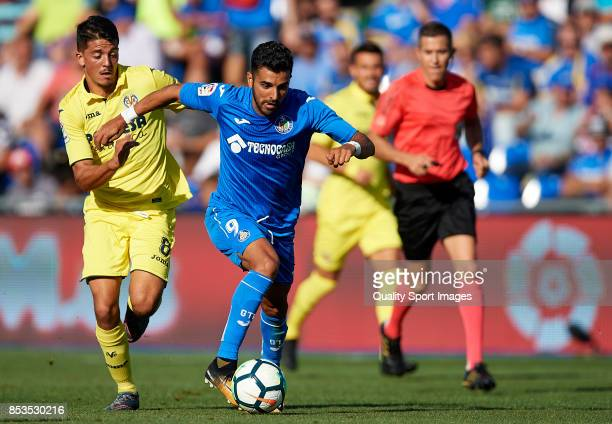 Angel Luis Rodriguez of Getafe competes for the ball with Pablo Fornals of Villarreal during the La Liga match between Getafe and Villarreal at...