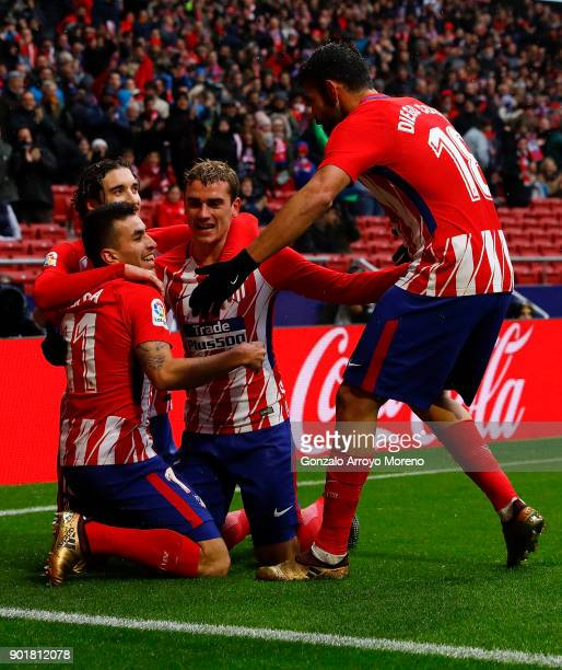 Angel Martin Correa of Atletico de Madrid celebrates scoring their opening goal with teammates Antoine Griezmann and Diego Costa during the La Liga...