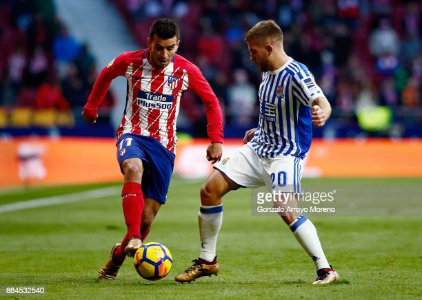 Angel Martin Correa of Atletico de Madrid competes for the ball with Kevin Rodrigues of Real Sociedad de Futbol during the La Liga match between Club...