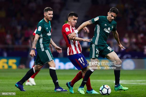 Angel Martin Correa of Atletico de Madrid competes for the ball with Marc Bartra of Real Betis Balompie during the La Liga match between Club...