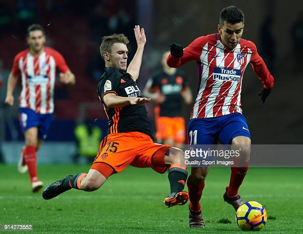 Angel Martin Correa of Atletico de Madrid is tackled by Lato of Valencia during the La Liga match between Atletico Madrid and Valencia CF at Wanda...