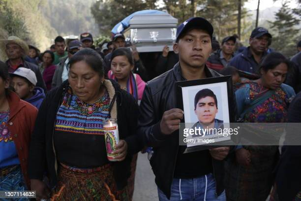 Angel Mauricio cousin of Rivaldo Danilo Jimenez holding his picture on March 14, 2021 in Comitancillo, Guatemala. 19 shot and charred bodies were...