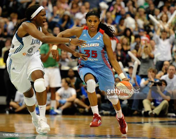 Angel McCoughtry of the Atlanta Dream brings the ball down court against Taj McWilliamsFranklin of the Minnesota Lynx in the second quarter in Game...