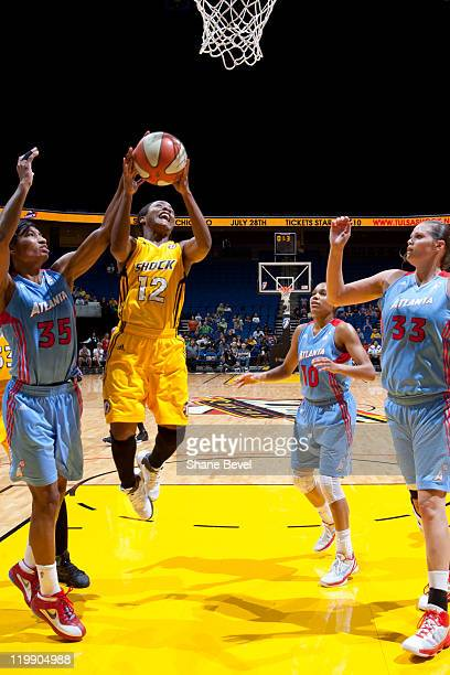 Angel McCoughtry of the Atlanta Dream tries to block a shot by Ivory Latta of the Tulsa Shock during the WNBA game on July 26 2011 at the BOK Center...