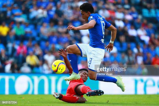 Angel Mena of Cruz Azul jumps over Omar Tejeda of Lobos BUAP during the 14th round match between Cruz Azul and Lobos BUAP at Azul Stadium on April 7...