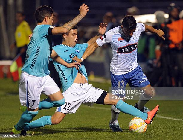 Angel Mena of Ecuator's Emelec vies for the ball with Pablo Varela and Clever Reyes of Uruguay's Juventud during their Sudamericana Cup football...